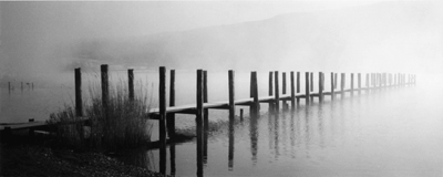 Wooden boat banding leading into in mist on Ullswater, Watermillock in Lake District
