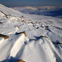 Sculpted snow and ice, Swirral Edge, Helvellyn with High Street glowing in the distance, Lake District