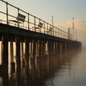 Sun breaking through morning mist at Pooley Bridge Old Pier, Ullswater in winter