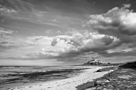 Bamburgh castle and beach with sun and dramatic clouds