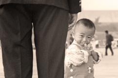 Small boy standing beside policeman in Tiananmen Square, 2000