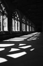 Sunlight pouring through cloisters of Durham Cathedral producing strong shadows of the tracery on stone walkway