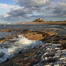 Bamburgh Castle and waves from Harkess Rocks