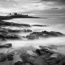 Dunstanburgh Castle in late afternoon light at high tide with waves spilling on rocks on Craster side, Northumberland