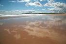 White clouds and blue sky reflected in wet sands of Embleton Beach, Northumberland on a beautiful sunny day