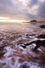 Sunrise at Bamburgh Beach, Northumberland with dawn light on waves and Bamburgh Castle in background