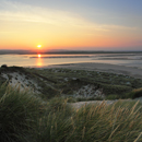 View of sunset over the dunes of Budle Bay from Budle Point, Northumberland, Northumbria